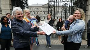 Tara MacDarby presents People Before Profit's Brid Smith with a petition for Leo Varadkar calling for an extension of maternity leave (Brian Lawless/PA)