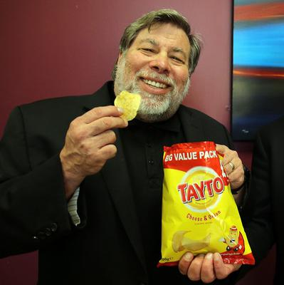 Steve Wozniak, the co-founder of Apple tries a bag of Tayto crisps after speaking at the Millennium forum in Derry