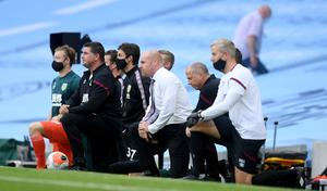Burnley manager Sean Dyche and his staff take the knee before the Premier League match at Manchester's Etihad Stadium (Michael Regan/PA)