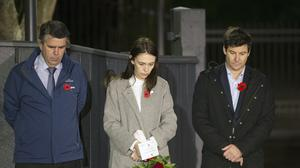 New Zealand Prime Minister Jacinda Ardern stands at dawn on the driveway of Premier House with her father Ross Ardern, left, and partner Clarke Gayford to commemorate Anzac Day in Wellington, New Zealand (Ross Giblin/Dominion Post/AP)