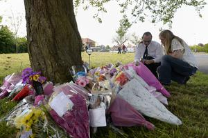 A couple light candles at the scene where 13-year-old Amber Peat was found (Joe Giddens/PA Wire)
