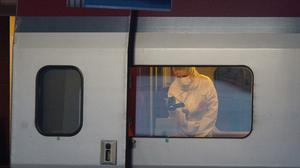 A police officer videos the crime scene inside a Thalys train at Arras train station (AP)