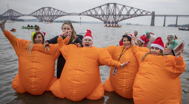 People take part in the Loony Dook New Year's Day dip in the Firth of Forth at South Queensferry (Jane Barlow/PA)