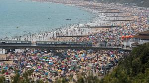 People on Bournemouth beach as the Met Office said Friday was the third hottest day on record (Steve Parsons/PA)
