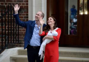 The delighted couple acknowledge the cheers of royal fans as they emerge from the hopsital with the prince (Kirsty O'Connor/PA)