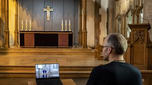 A parishioner watches a laptop inside Liverpool Parish Church (Our Lady and St Nicholas), during the Church of England's first virtual Sunday service (PA)