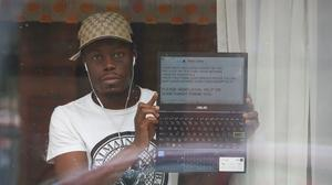 A man holds his laptop up at a window of the Radisson Blu hotel near Heathrow, displaying a message to the media outside (Jonathan Brady/PA)