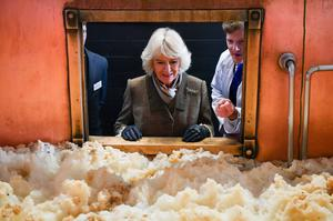 The Duchess of Cornwall looks at fermenting beer in a fermenting vessel (Ben Birchall/PA)