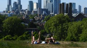 Two women enjoy the hot weather in Greenwich Park, London (Kirsty O'Connor/PA)