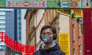 A member of the Chinese community in Manchester wearing a face mask in January (Peter Byrne/PA)