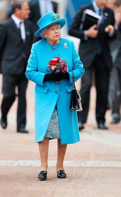The Queen looks up at the statue of the Queen Mother which she unveiled in the town of Poundbury