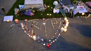 People leave tributes and light candles by City Hall in Manchester for victims of the concert bomb attack (Ben Birchall/PA)