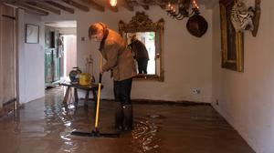 A resident cleans up in Cossington, Leicester, as floodwaters cover the ground floor in her home (Joe Giddens/PA)