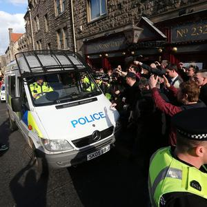 A police van carrying Mr Farage makes its way through protesters and a crowd of media in Edinburgh