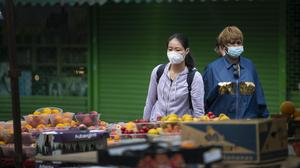 A woman wearing a face mask looks at an outdoor fruit and veg market stall in Walthamstow (PA)
