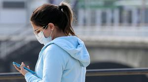 A woman wearing a mask looks at her phone under a sign saying 'Stay Home' projected from Bournemouth pier, as the UK continues in lockdown to help curb the spread of the coronavirus.