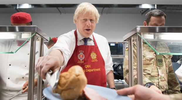 Prime Minister Boris Johnson serves Christmas lunch to British troops stationed in Estonia (Stefan Rousseau/PA)
