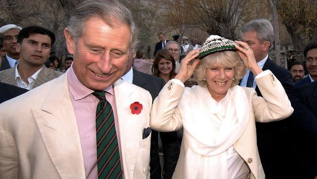 The Prince of Wales watches as the Duchess of Cornwall wears a hat given to her as a present from the villagers of Nansoq in northern Pakistan (John Stillwell/PA)