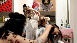 Carole Rickaby (centre left) cuts the hair of customer Sandra Jacobs (centre right) at Tusk Hair, in Camden, North London, after opening at midnight to the first post-lockdown customer as restrictions are eased across England (Jonathan Brady/PA)