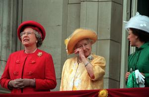The Queen Mother, alongside the Queen and Princess Margaret, wipes her eye as she stands on the balcony of Buckingham Palace on the 50th anniversary of VE Day in 1995 (PA)