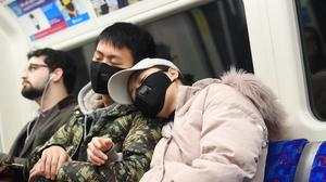 A man and a woman wearing a face masks while traveling on a tube train (Victoria Jones/PA)