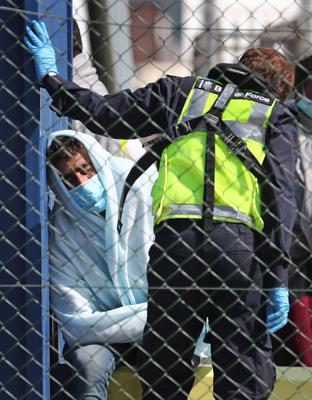 A man thought to be a migrant is processed by Border Force officers after being brought to shore in Dover (Gareth Fuller/PA)
