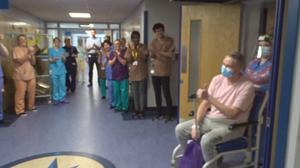 Charge nurse David Courtney-Williams gives colleagues the thumbs up as he is clapped out of Morriston Hospital (Swansea Bay UHB)