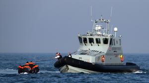 Border Force officers assist 20 Syrian migrants aboard HMC Hunter after they were stopped as they crossed The Channel in an inflatable dinghy headed in the direction of England. (Gareth Fuller/PA)