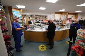 Pharmacist Andrew Hodgson (left) speaks to Robert Salt (centre), 82, before he receives an injection of the coronavirus vaccine at Andrews Pharmacy in Macclesfield (Peter Byrne/PA)