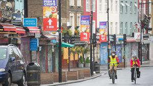 Cyclists ride past shuttered shops on Camden High Street, in north London (Dominic Lipinski/PA)