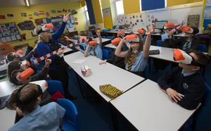 Pupils and their teacher at St John's Primary, Barrhead, test out the devices (ERC/PA)