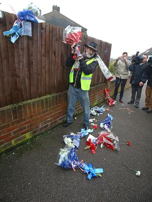 Mr Gordon pulls the flowers down from a fence (Gareth Fuller/PA)