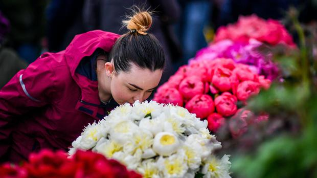 A woman smells some flowers in Cardiff (PA)