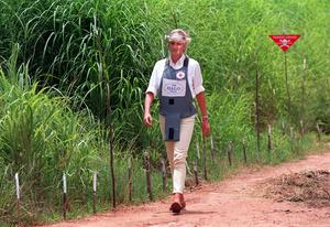 Diana, Princess of Wales, walks alongside a minefield wearing body armour during her visit to Angola in January 1997 (John Stillwell/PA)