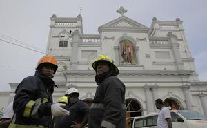 Firefighters near St Anthony's Shrine after a blast in Colombo, Sri Lanka (Eranga Jayawardena/AP)