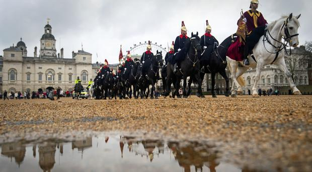 Puddles on the parade ground for the changing of the guard in London (Victoria Jones/PA)