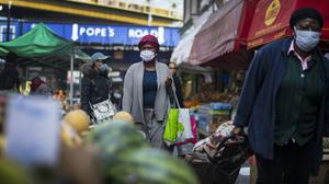 A woman in a protective face mask walks through Brixton Market in south London (PA)