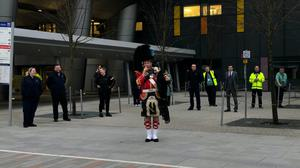 Alasdair Henderson plays the bagpipes outside the Queen Elizabeth University Hospital in Glasgow (Douglas Barrie/PA)