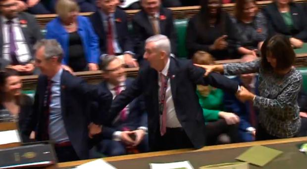 Sir Lindsay Hoyle (centre) is dragged to the speaker's chair after becoming the new Speaker of the House of Commons