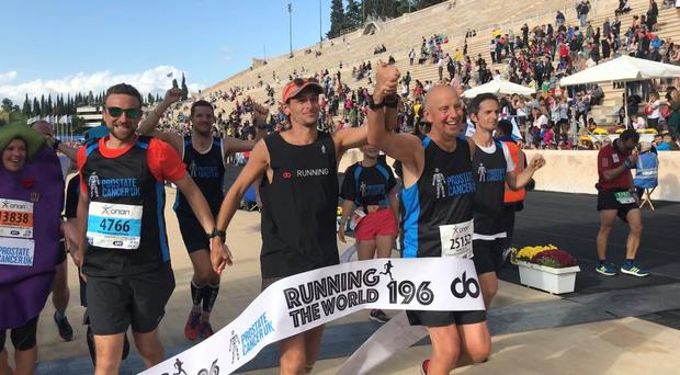 Nick Butter (centre) finishes his final marathon in Athens (Prostate Cancer UK)