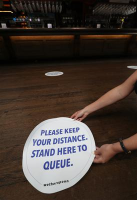 Social distancing signs on the floor of Wetherspoons pub The Mossy Well in Muswell Hill, London (Yui Mok/PA)