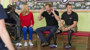 Embargoed to 0001 Wednesday April 27Prince Harry reacts to the audience of children as he sits flanked by presenter Di Dougherty and rowing competitor Scott Meenagh, who lost both his legs after stepping on an IED in Afghanistan, as they take part in filming for the Sky Sports 'Game Changers' television show dedicated to the Invictus Games at Lambs Lane Primary School in Spencers Wood, near Reading.