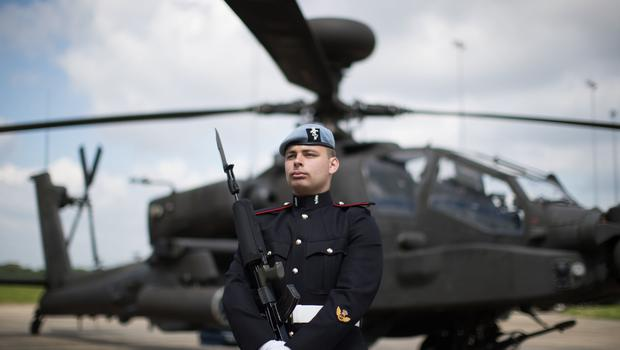 Craftsman Dekin, a Royal Electrical Engineer of 3 Regiment Army Air Corps in front of an Apache helicopter at Wattisham Airfield (Aaron Chown/PA)
