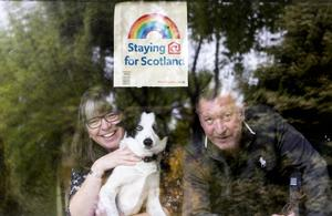 Colin and Margaret Moncur, with their dog Molly, look out from their window in Minard (Jane Barlow/PA)