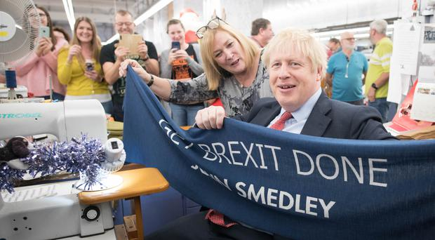 Prime Minister Boris Johnson holds up a banner with the words Get Brexit Done during a visit to the John Smedley Mill in Matlock, Derbyshire (Stefan Rousseau/PA)