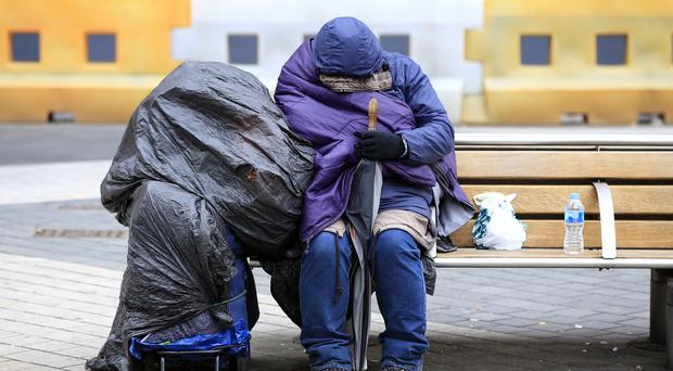 A homeless person rests on a bench outside Imperial College, London (Jonathan Brady/PA)
