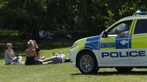 Police officers in a patrol car move sunbathers on in Greenwich Park, London (Yui Mok/PA)