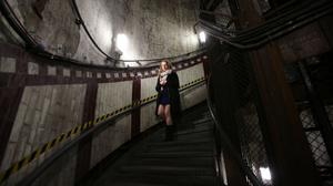 A visitor descends the steps of Down Street disused underground station in Mayfair