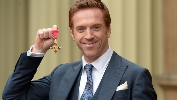 Actor Damian Lewis holds his Officer of the Order of the British Empire (OBE) after the investiture ceremony at Buckingham Palace