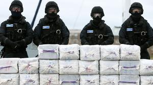 Members of the navy stand behind the drugs haul taken from the yacht Makayabella